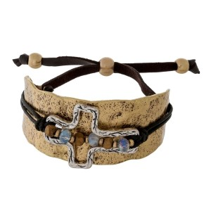Hammered, burnished metal bracelet with a beaded, two tone cross focal and a black cord tie.