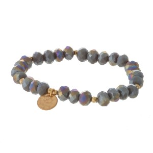 Faceted bead stretch bracelet with a hammered gold tone circle charm.