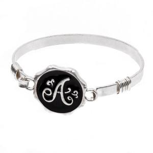 Metal bracelet with letter focal.