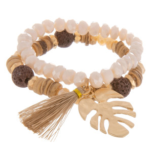 "Layered beaded bracelet with natural stone and leaf with tassel charm. Approximate 6"" in length."
