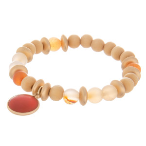 "Natural stone stretch bracelet with wood bead detail and natural stone charm. Approximate 6"" in length."