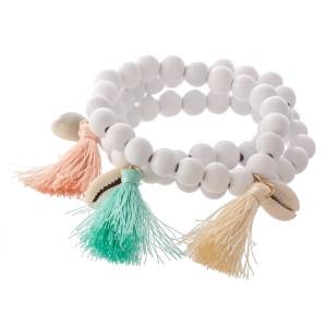 "Wood Beaded Puka Shell Tassel Stretch Bracelet Set.  - 3pcs/set - Approximately 3"" in diameter - Fits up to a 7"" wrist"