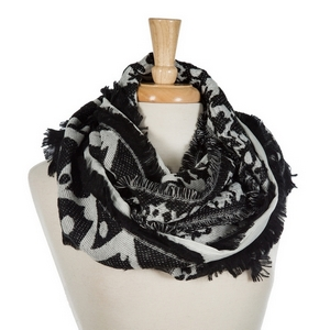"""Black and ivory printed infinity scarf with frayed edges. 100% acrylic. Measures 36"""" x 18"""" in size."""