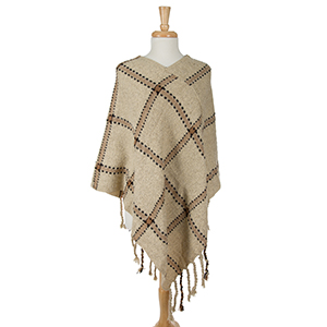 Ivory poncho with a plaid design and tassel accents. 100% acrylic. One size fits most.