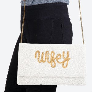 """High Quality Ivory Seed Beaded """"Wifey"""" Crossbody Clutch.  - Open lined inside - 1 open functional pocket - Fold over flap button closure - Approximately 10"""" W x 6"""" T - Strap hangs 21"""" L - 100% Cotton"""
