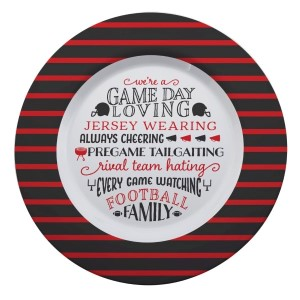 """Gameday melamine plate in black and red, that reads """"We're a game day loving, jersey wearing, always cheering, pregame tailgating, rival team hating, every game watching, football family. Measures 14"""" in diameter and is dishwasher safe."""