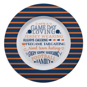 """Gameday melamine plate in navy and orange, that reads """"We're a game day loving, jersey wearing, always cheering, pregame tailgating, rival team hating, every game watching, football family. Measures 14"""" in diameter and is dishwasher safe."""