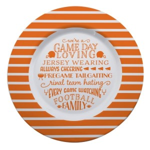 """Gameday melamine plate in orange and white, that reads """"We're a game day loving, jersey wearing, always cheering, pregame tailgating, rival team hating, every game watching, football family. Measures 14"""" in diameter and is dishwasher safe."""