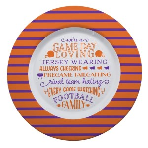 """Gameday melamine plate in purple and white, that reads """"We're a game day loving, jersey wearing, always cheering, pregame tailgating, rival team hating, every game watching, football family. Measures 14"""" in diameter and is dishwasher safe."""