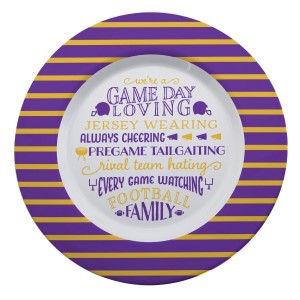"""Gameday melamine plate in purple and yellow, that reads """"We're a game day loving, jersey wearing, always cheering, pregame tailgating, rival team hating, every game watching, football family. Measures 14"""" in diameter and is dishwasher safe."""