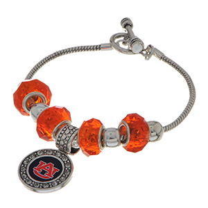 "Officially licensed 7"" Silver tone toggle closure charm bracelet featuring an Auburn logo charm accented by orange and silver tone sliding charms."